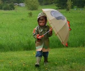 Rompicapo di Bambino con il suo ombrello e giacca pioggia in pioggia di primavera