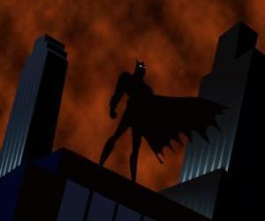 Rompicapo di Batman, il uomo pipistrello, guardando la città dal tetto di un edificio a Gotham City
