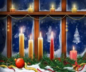 Rompicapo di candele di Natale illuminata davanti ad una finestra