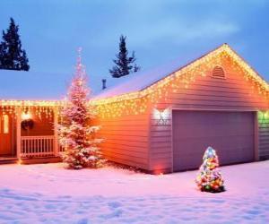 Rompicapo di Casa decorata con decorazioni natalizie e di due alberi di Natale nel giardino