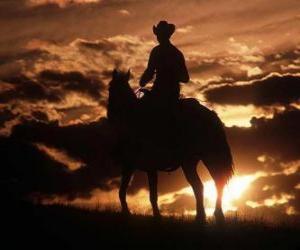 Rompicapo di Cowboy equitazione o al crepuscolo