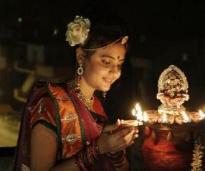 Rompicapo di Donna in ginocchio con un olio della lampada in mano nella celebrazione del Diwali