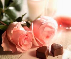 Rompicapo di Due rose rosa con due a forma di cuore cioccolatini