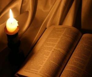 Rompicapo di La Bibbia e una candela accesa su l'altare