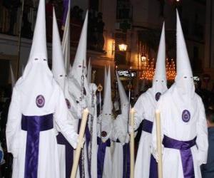 Rompicapo di Nazareni o  penitenti in una processione durante la Settimana Santa con il cappuccio o un cono, tunica e mantello