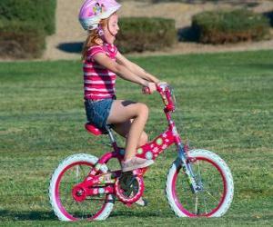 Rompicapo di Ragazza in bicicletta nel parco in primavera