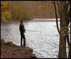 Pesca - Pescatore di fiume in azione in un paesaggio boscoso