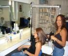 Parrucchiere pettinatura e l'asciugatura i capelli ad una cliente nel salone di bellezza o il parrucchiere