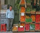 Venditore di frutta e verdura nel loro negozio