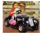 Ragazza in una classica vettura giocattolo