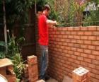 Un muratore che alza una parete