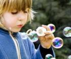 Bambina che gioca a fare bolle di sapone