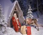 Santa alla porta della sua casa con una renna e regali