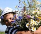 Un bambino con un dono per sua madre, un gran mazzo di fiori