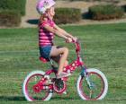 Ragazza in bicicletta nel parco in primavera