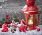 Lampada di Natale con candela acesa e decorazione di agrifoglio