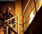 Vigile del fuoco su una scala in fiamme