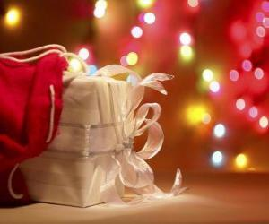 Rompicapo di Regalo di Natale avvolto in carta bianca e decorato con un arco