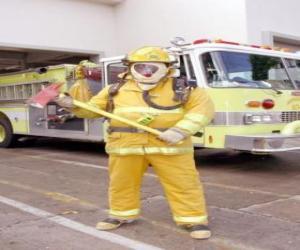 Rompicapo di Vigile del fuoco completamente attrezzata con l'ascia in mano contro il camion